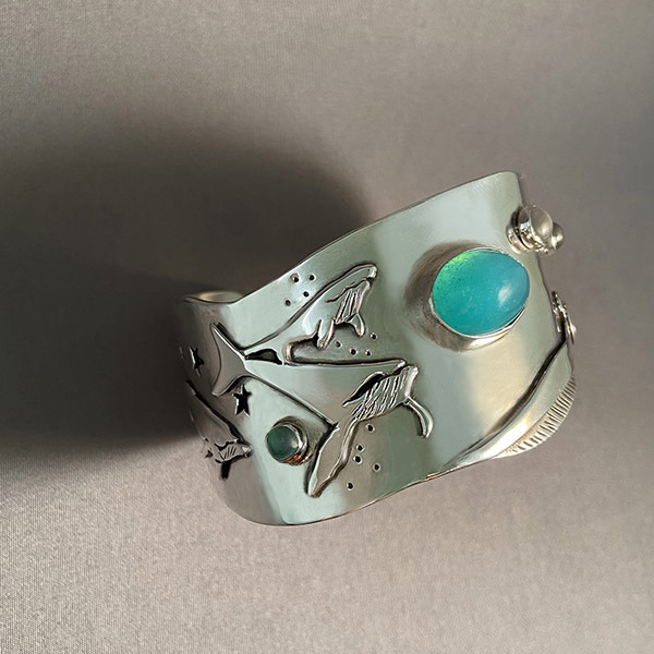Bracelet by Nadine Zenobi showing a whale with green and blue stones